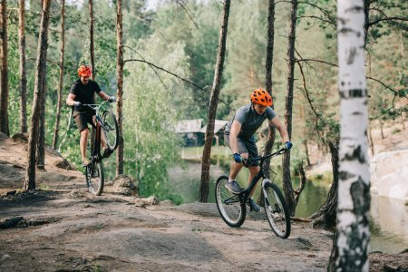 male extreme cyclist in protective helmet balancing on back wheel of mountain bicycle while his friend riding near in forest