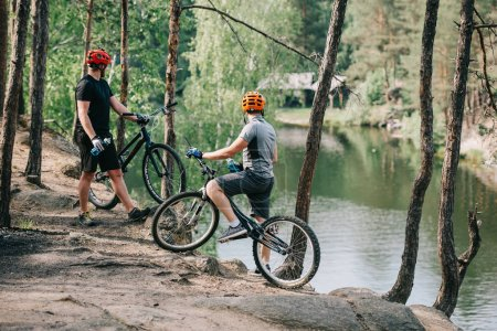rear view of male extreme cyclists in helmets with mountain bikes resting with sport bottles of water and looking at river in forest