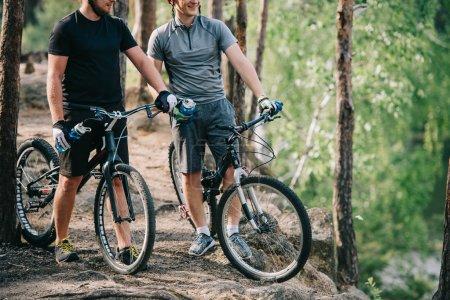 Photo pour Cyclistes extrêmes masculins dans des casques avec des vélos de montagne reposant avec des bouteilles d'eau de sport dans la forêt - image libre de droit