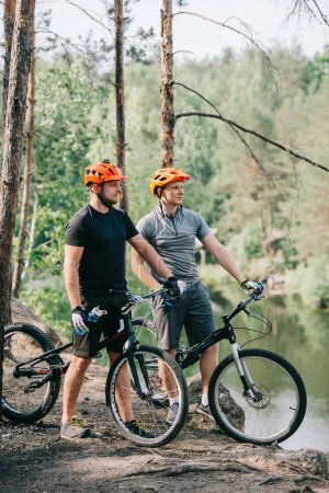 male trial bikers in helmets with mountain cycles resting with sport bottles of water near river in forest