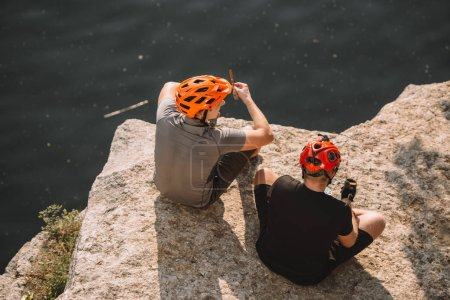 male hikers in protective helmets resting and eating canned food on rocky cliff over river