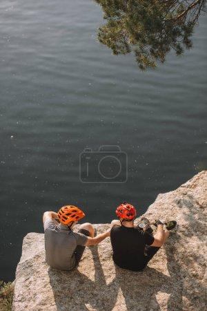 Foto de Vista de ángulo alto de excursionistas masculinos en cascos protectores comer enlatados en acantilado rocoso sobre el río - Imagen libre de derechos