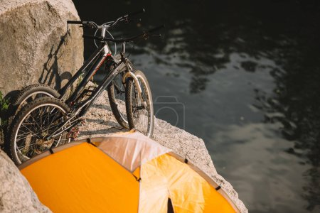 high angle view of mountain bicycles and travel tent on rocky cliff over river