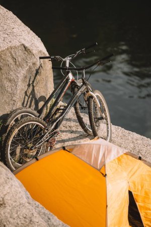 scenic view of two mountain bicycles and tourist tent on rocky cliff over river