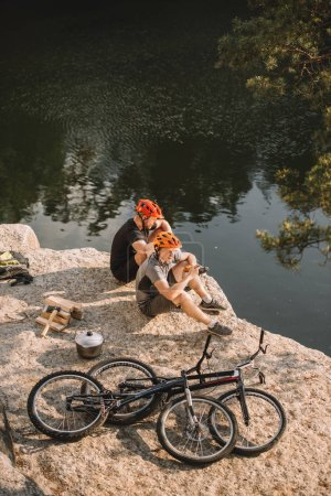 Photo for Two trial bikers resting near logs, cauldron and mountain cycles on rocky cliff over river - Royalty Free Image