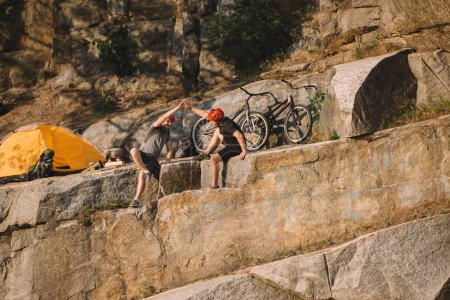 Photo for Trial bikers resting and giving high five to each other near tent and mountain cycles on rocky cliff - Royalty Free Image