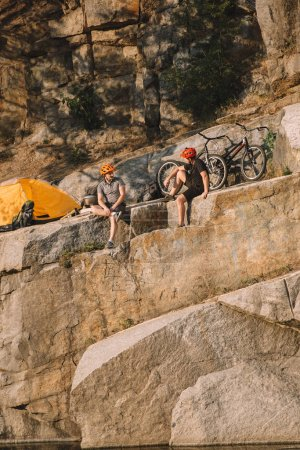 two male travelers in protective helmets resting near tent and bicycles on rocky cliff