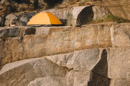 scenic view of tourist tent on rocky cliff during daytime