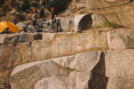 male traveler in protective helmet standing with mountain bike and pointing by finger to friend near tent on rocky cliff