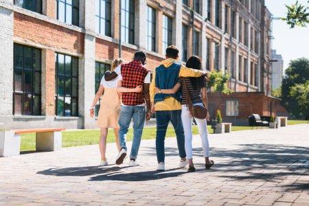 Photo pour Vue arrière d'un groupe multiculturel d'amis qui se câlinent en marchant ensemble dans la rue - image libre de droit