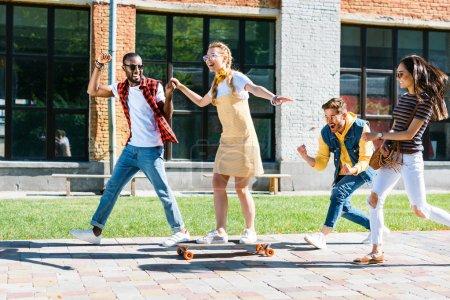 multiracial friends with long board having fun while spending time together on street