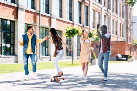 happy multiracial friends with long board having fun while spending time together on street