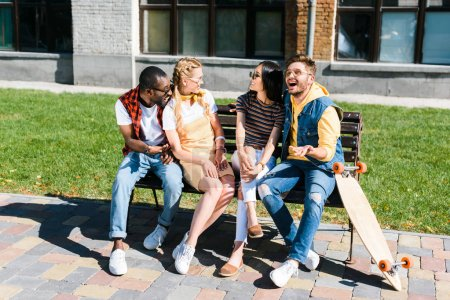 cheerful multicultural couples resting on bench together on street