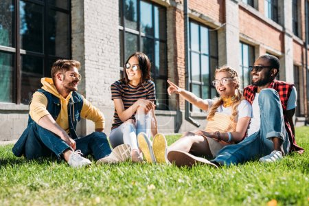 multiethnic group of friends resting on green grass in city