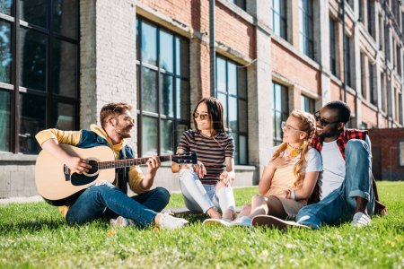 interracial group of friends with acoustic guitar resting on green grass on summer day