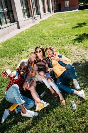 multiethnic friends taking selfie on smartphone while resting on green lawn together