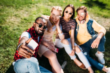 selective focus of multiethnic friends taking selfie on smartphone while resting on green lawn in park