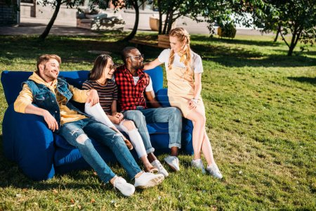 smiling interracial friends resting on blue sofa together in park