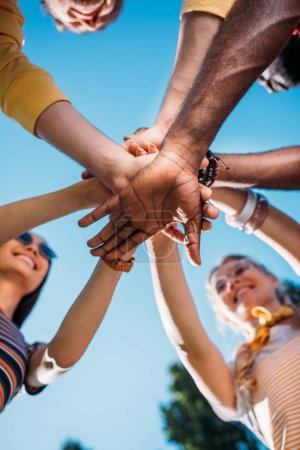 Foto de Vista inferior del multirraciales amigos jóvenes cogidos de la mano junto con cielo azul sobre fondo - Imagen libre de derechos