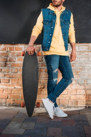 cropped shot of man with longboard standing on street