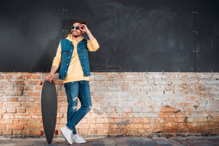stylish man in sunglasses with longboard standing on street