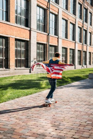 back view of man with american flag skating on longboard on street