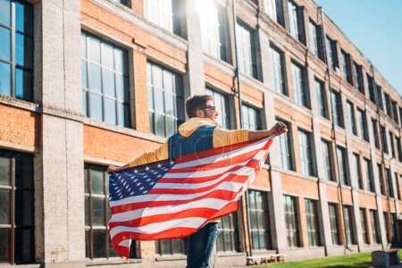 back view of young man with american flag in hands on street