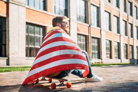 back view of young man with american flag sitting on longboard on street