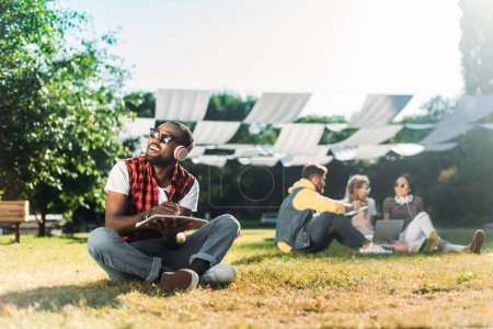 selective focus of african american man in headphones with notebook resting on green grass with multiracial friends with laptop behind