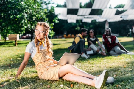 selective focus of young smiling woman with laptop and multiracial friends behind resting on green grass in park