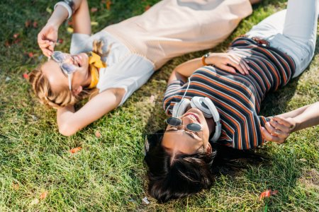 multicultural young smiling women resting on green grass in park