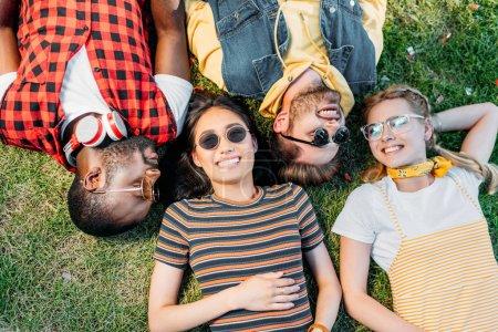 Photo pour Vue aérienne d'amis multiethniques heureux reposant sur la pelouse verte ensemble - image libre de droit