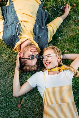 Photo for Overhead view young happy couple resting on green grass in park - Royalty Free Image