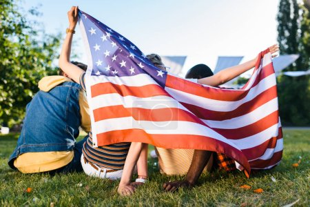 back view of multiracial friends with american flag sitting on green grass in park