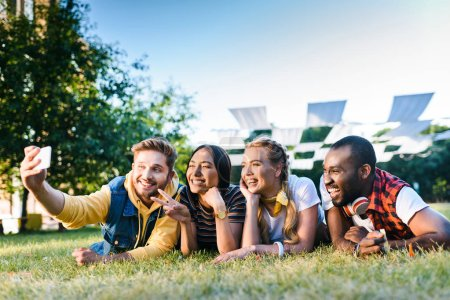 portrait of multiethnic cheerful friends taking selfie on smartphone while resting on green grass in park
