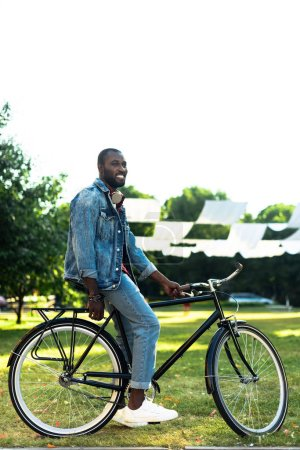 side view of smiling african american man with retro bicycle in park