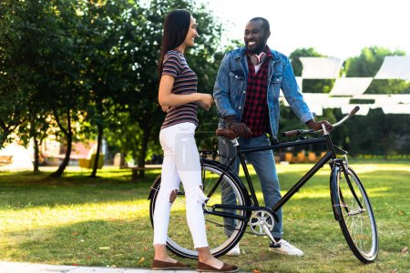 Photo for Smiling multiracial couple with retro bicycle having conversation in park - Royalty Free Image