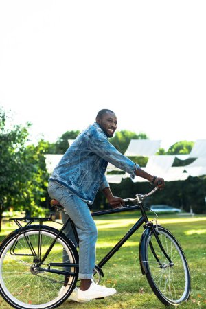 smiling african american man riding retro bicycle in park