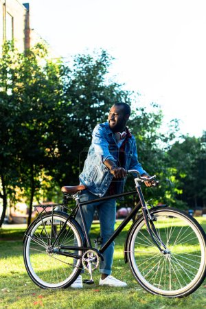smiling african american man with retro bicycle in park