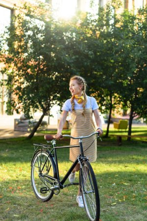 young beautiful woman with retro bicycle in park