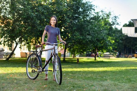 young asian woman with retro bicycle in park