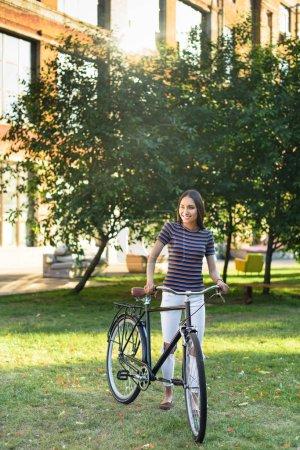 Foto de Joven asiática con una bicicleta retra en Parque - Imagen libre de derechos