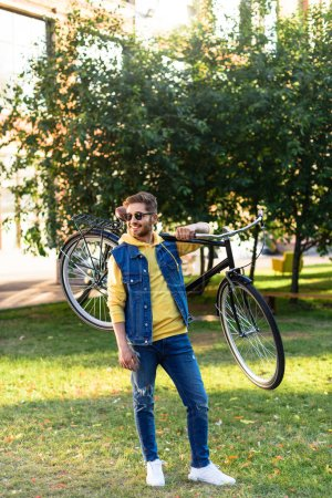 young cheerful man in sunglasses with retro bicycle in park