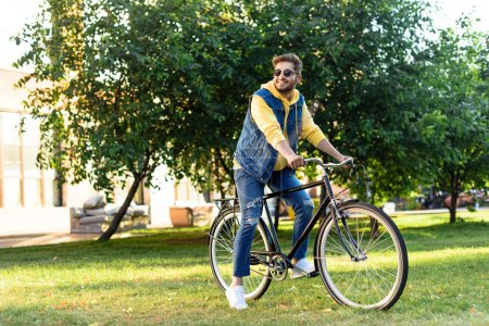 young smiling man in sunglasses riding retro bicycle in park