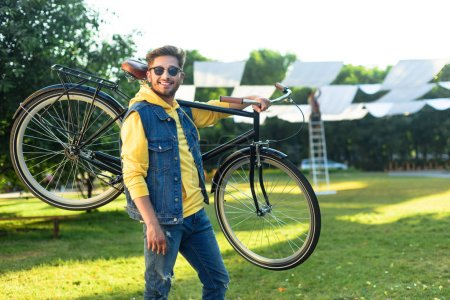 Photo for Young smiling man in sunglasses with retro bicycle in park - Royalty Free Image