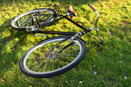 close up view of retro bicycle lying on green grass in park