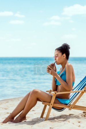 young african american woman in bikini and sunglasses drinking cocktail in coconut shell while sitting on deck chair in front of sea