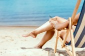 cropped image of woman holding cocktail in coconut shell and laying on deck chair on sandy beach