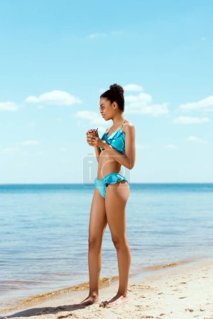 Photo for Young african american woman in bikini and sunglasses holding cocktail in coconut shell on sandy beach - Royalty Free Image