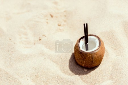 selective focus of cocktail in coconut shell on sandy beach